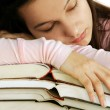 Tired girl sleeping on books stack — Stockfoto