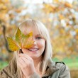 Young woman with autumn leaf — Stock Photo