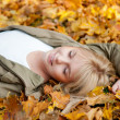 Young woman dreams in autumn leaves — Stock Photo