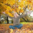 Young woman playing with autumn leaves — Stock Photo