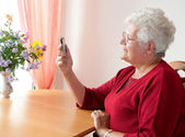 Old woman with cell phone — Stockfoto