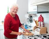 Oude vrouw in de keuken — Stockfoto