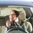 Womwith lipstick and cell phone in car — Stock Photo #9784714