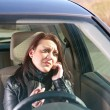Woman with cigarette and cell phone in the car — Stock Photo