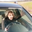 Annoyed woman in the car - Stock Photo