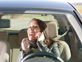 Woman with lipstick and cell phone in the car — Stockfoto