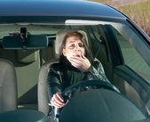 Woman yawns in the car — Stock Photo