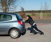 Woman pushes her car — Stockfoto