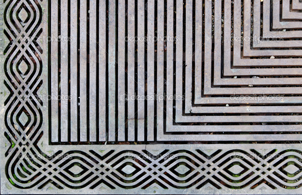 Corner of an ornately designed steek grating on the sidewalk — Stock Photo #9091988