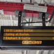 Electronic Timetable on London Railway Platform with Security Ca - Stock Photo