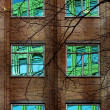 Reflection of Colourful Building in Windows of Old Block - Stock Photo