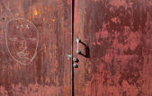 Graffit and peeling paint on old red steel door — Stock Photo