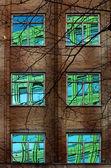 Reflectie van kleurrijke gebouw in windows van oude blok — Stockfoto