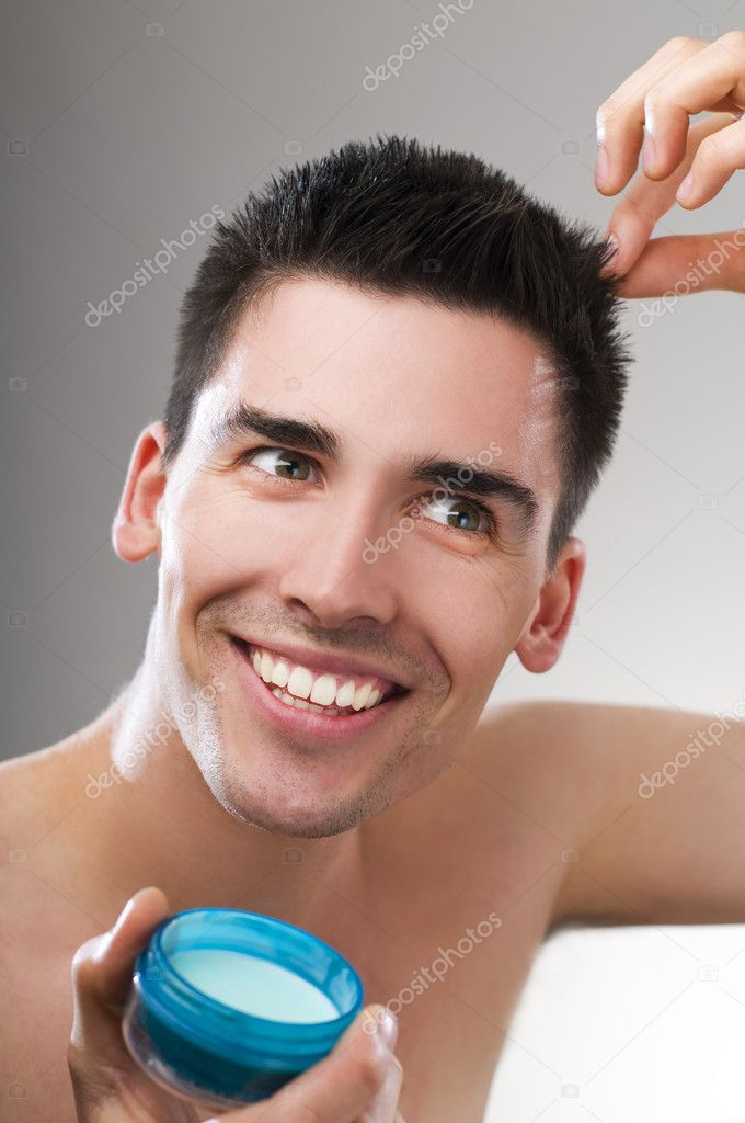 Young handsome man applying hair gel close up  Stock Photo #8704193