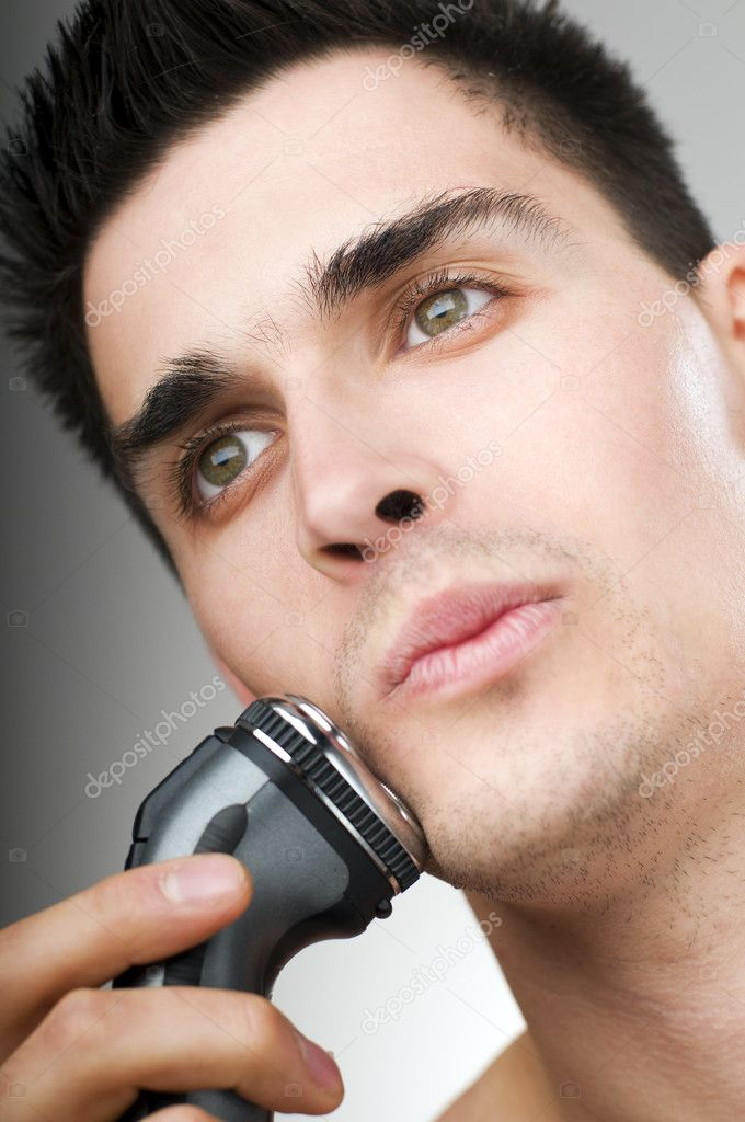 Young man shaving his beard off with an electric razor  Stock Photo #8720042