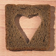 Piece of black bread with the cut out pulp in the form of heart — Zdjęcie stockowe