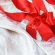 Foto Stock: Gift Box with Red Ribbon over Silk