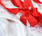 Gift Box with Red Ribbon over Silk — Stock Photo