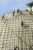 Closeup of construction worker assembling scaffold on building s — Stok fotoğraf