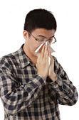 Young man with a cold blowing nose on tissue — Stock Photo