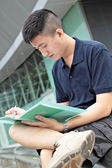 Casual asian businessman texting on his book. — Stock Photo