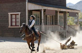 Sheriff dragging a Bandit by rope from his horse — Stock Photo