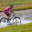 Stock Photo: Cyclist at the speed of moving mountain river
