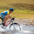Cyclist at the speed of moving mountain river — Stock Photo #10164725