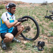 Biker changing a flat tire on desert mountain bike competition - Stock Photo