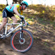 Mountain bike competition in autumn forest - Stock Photo