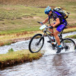 Cyclist at the speed of moving mountain river — Stock Photo