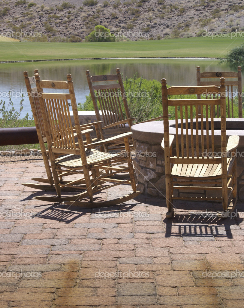 Wooden rocking chairs, surrounding a firepit invite conversation beside a golf course pond.  Stock Photo #10505928