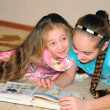 Foto Stock: Two girls read book