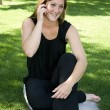 Beautiful Girl in the Park in a Black Dress Talking on the Phone — Stock Photo