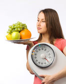 Young woman holding a weight scale and plate with fresh fruit — Stock Photo