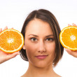 Young woman holding two halves of orange — Stock Photo