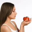 Young woman looking at a fresh tomato in her hands — Stock Photo