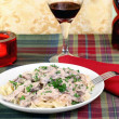 Beef Stroganoff and egg noodles with wine and a lit candle. — Stock Photo