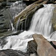 Stock Photo: Veiled waterfall in rocky glen in mountains.
