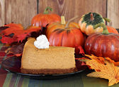 Pumpkin cheesecake in autumn setting — Stock Photo