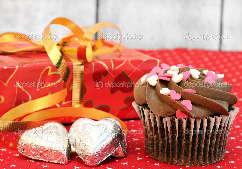 Chocolate decorated cupcake, pretty wrapped gift and candy for Valentines Day.  Close up with selectivefocus on cupcake.  Stock Photo #8771846