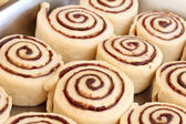Raw cinnamon buns ready to bake with selective focus. — Stock Photo