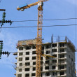 Electric pylon and building crane - Stock Photo