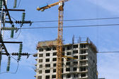 Electric pylon and building crane — Stock Photo