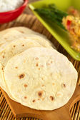 Indian flatbread called chapati on wooden board (Selective Focus, Focus on the big brown spot on the left) — Stock Photo