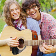 Teens having fun with guitar in park — Stock Photo