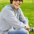 Funny teenager laughs in park - Stock Photo