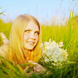 Pretty girl lying in park with flowers — Stock Photo #9986699