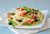 Spaghetti with tomato, capers and basil with olives — Photo