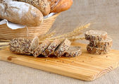 Diverse bread with slices of bread with grains — Stock Photo